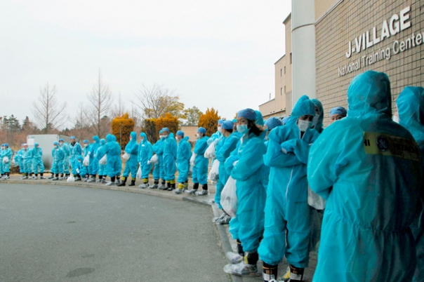 Workers wait for transportation to Tokyo Electric Power Co's Fukushima Daiichi nuclear power plant at J-Village near the plant in Fukushima